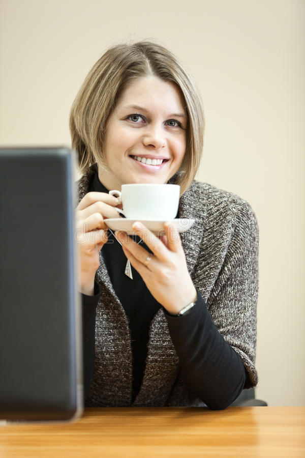 Lächelnde Schönheitsfrau, die Kaffeetasse in den Händen hält lizenzfreies stockbild