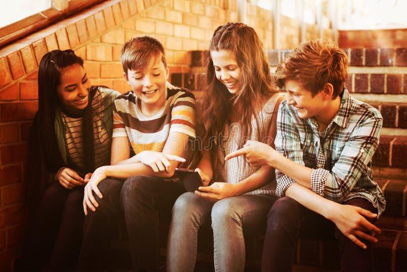 Lächelnde Schüler, die auf dem Treppenhaus unter Verwendung des Handys sitzen lizenzfreie stockfotografie