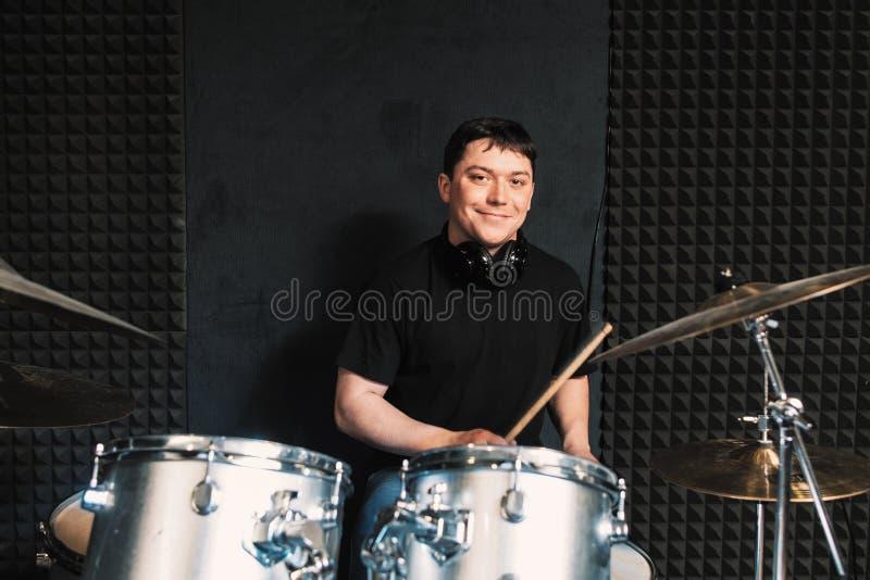 Lächelnde Schlagzeugerspiele auf Trommelsatz stockbild