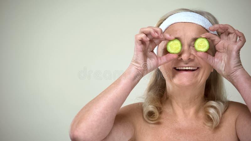 Lächelnde schließende Augen älterer Dame mit Scheiben der Gurke, skincare Verfahren stockbilder