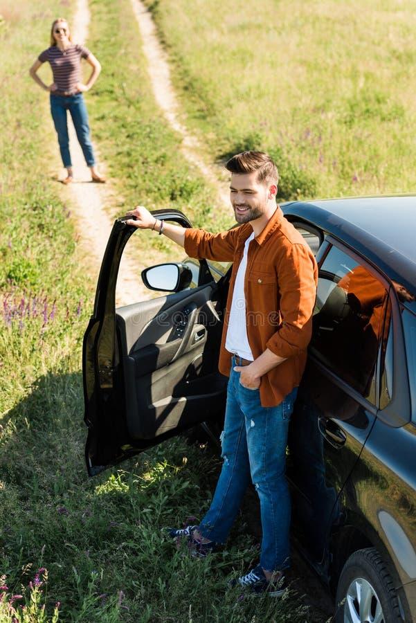 lächelnde schließende Tür des jungen Mannes des Autos und seiner Freundin lizenzfreie stockbilder