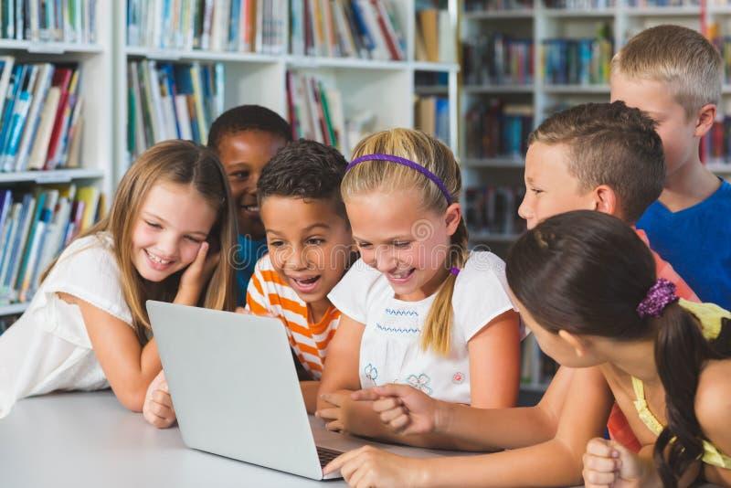 Lächelnde Schule scherzt das Betrachten des Laptops in der Bibliothek lizenzfreie stockbilder