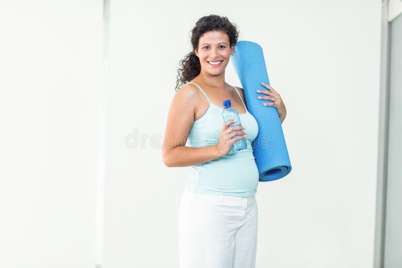 Lächelnde schwangere Frau, die Übungsmatte und Wasserflasche hält lizenzfreies stockbild