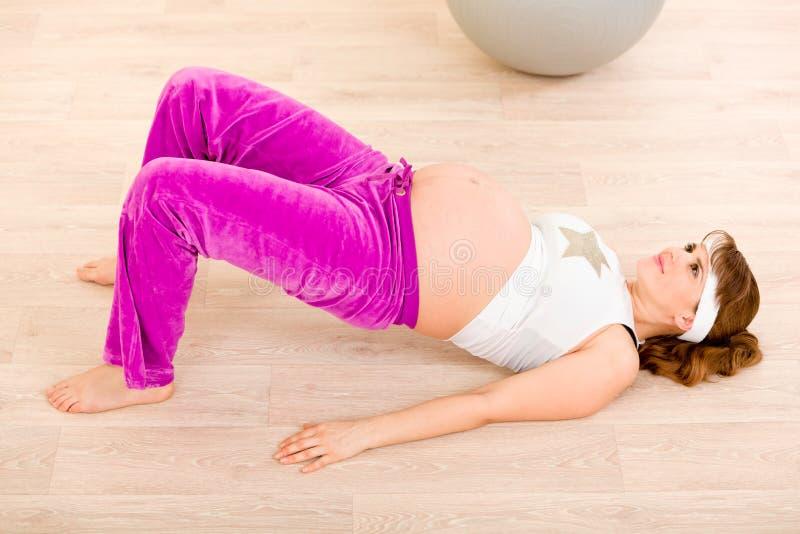 Lächelnde schwangere Frau, die Eignungübungen tut stockbilder