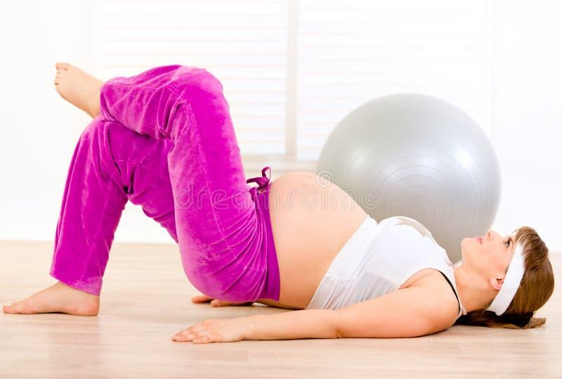 Lächelnde schwangere Frau, die zu Hause Gymnastik bildet stockfotografie