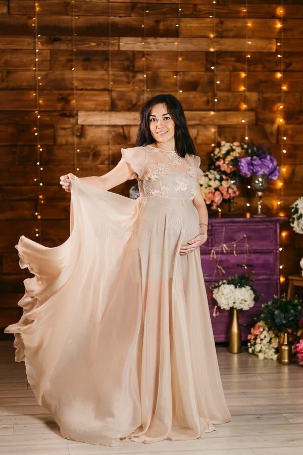 Lächelnde schwangere Schönheit in der vollen Höhe, welche die Kamera im Studio betrachtet lizenzfreie stockfotografie