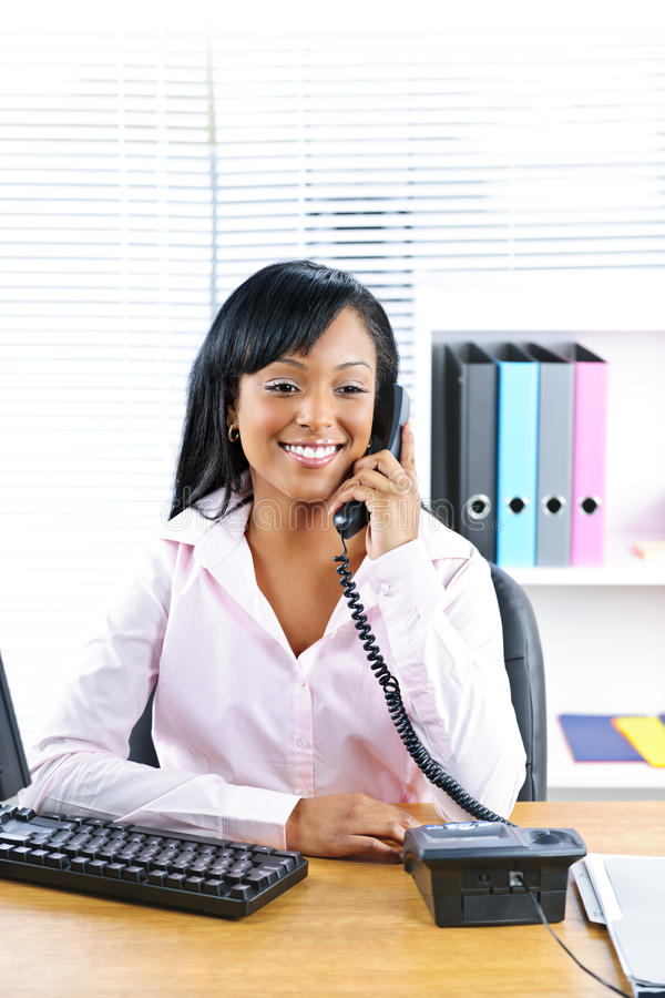 Lächelnde schwarze Geschäftsfrau am Telefon am Schreibtisch lizenzfreie stockfotos