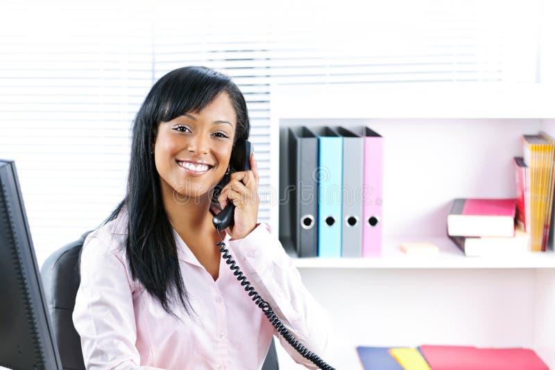 Lächelnde schwarze Geschäftsfrau am Telefon am Schreibtisch lizenzfreies stockfoto