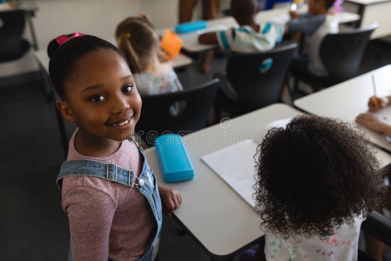Lächelnde schwarze Schulmädchenstellung und -c$betrachten der Kamera im Klassenzimmer lizenzfreies stockfoto
