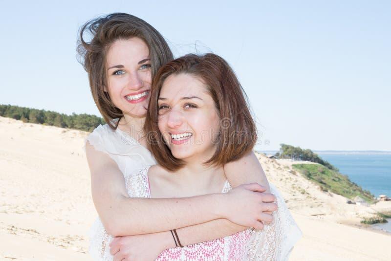 Lächelnde Schwestern, die auf Seehintergrund umarmen lizenzfreie stockfotos