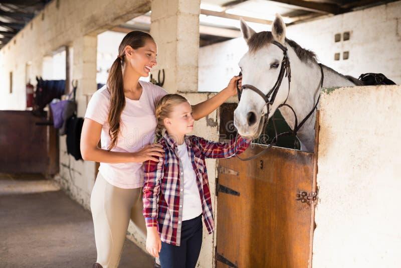 Lächelnde Schwestern, die Pferd streichen stockbild