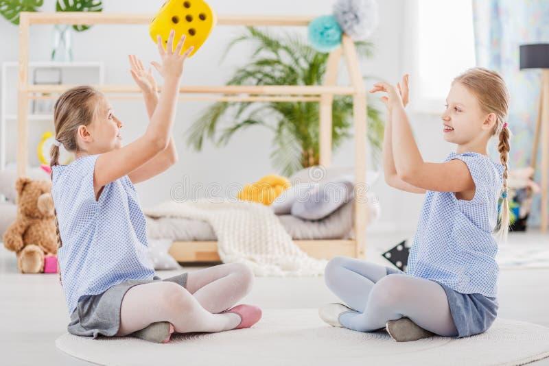 Lächelnde Schwestern, die zusammen spielen stockbild