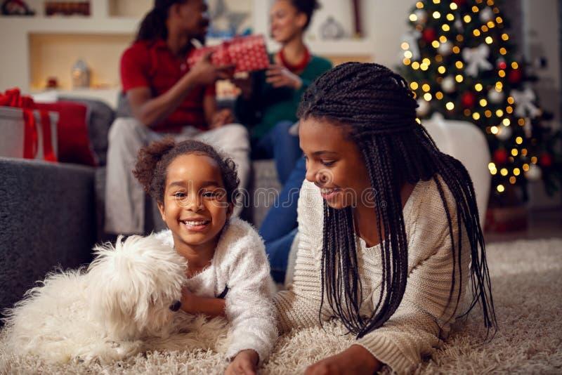 Lächelnde Schwestern spielen mit Hund, den sie auf Boden nea liegen stockfoto