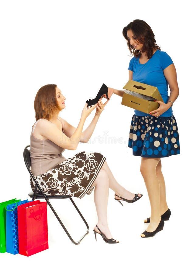 Lächelnde Sekretärin, die der Frau neuen Schuh zeigt stockfotos