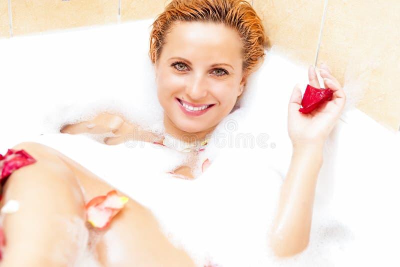 Lächelnde sexy kaukasische Frau, die im Bad sich entspannt lizenzfreies stockfoto
