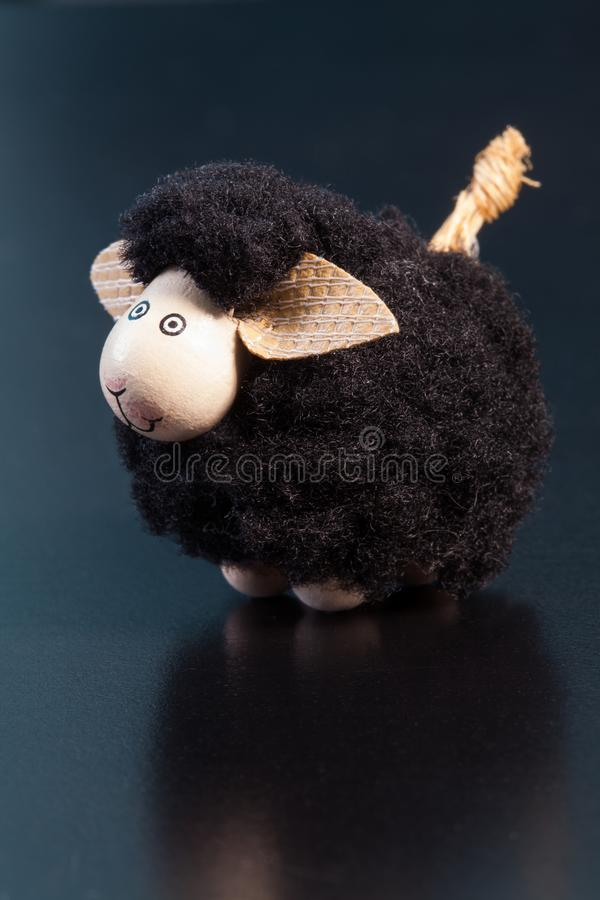 Lächelnde Spielzeugfigürchen der schwarzen Schafe mit den großen Ohren auf einer blauen Oberfläche lizenzfreies stockbild