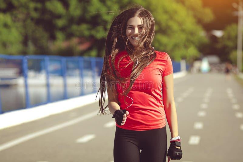 Lächelnde Sportfrau, die in Park läuft stockfotos