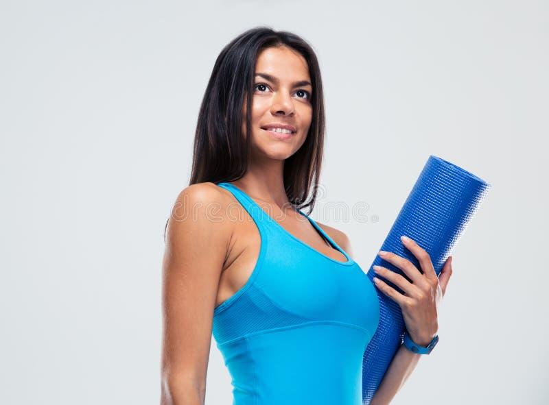 Lächelnde Sportfrau, die Yogamatte hält lizenzfreies stockfoto