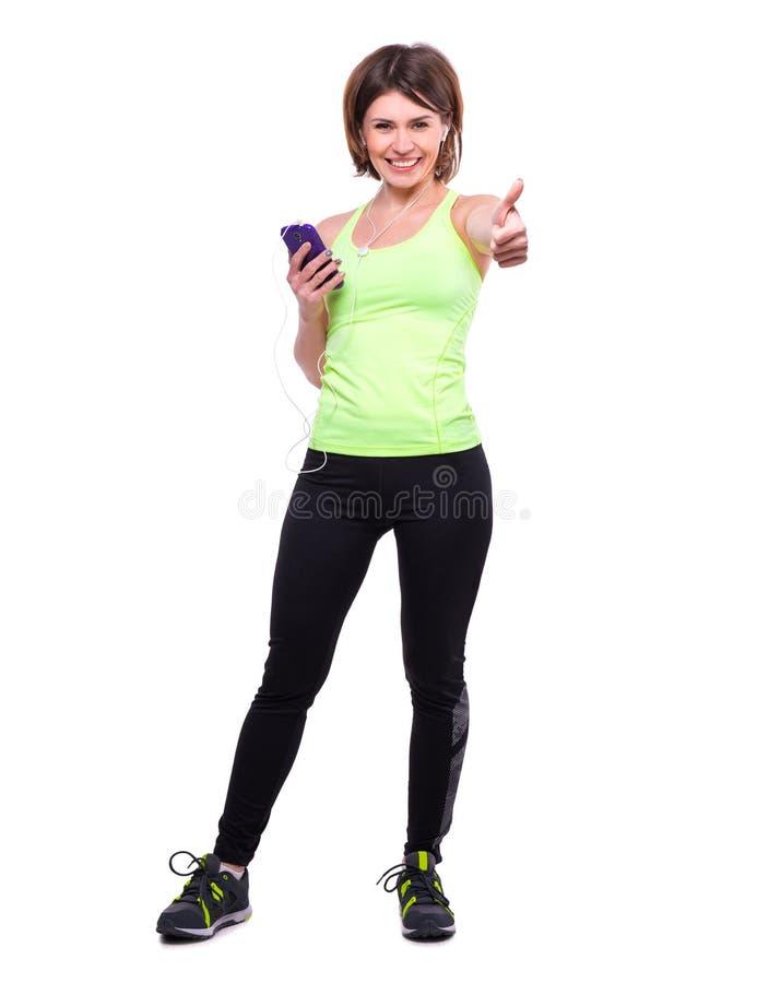 Lächelnde Sportfrau mit Mobile und mit ihrem Daumen oben lizenzfreies stockbild