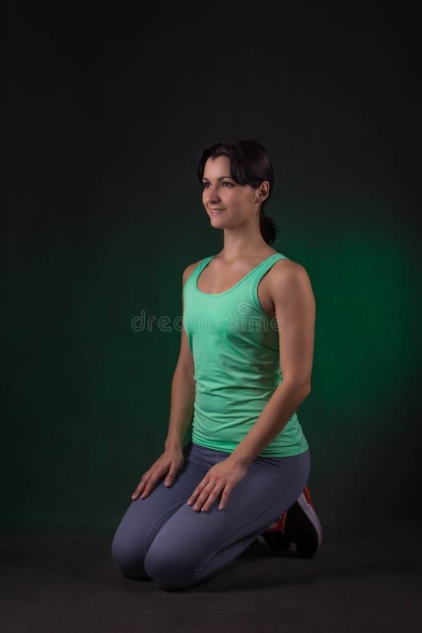 Lächelnde sportliche Frau, die auf einem dunklen Hintergrund mit grüner Hintergrundbeleuchtung sitzt lizenzfreie stockfotografie
