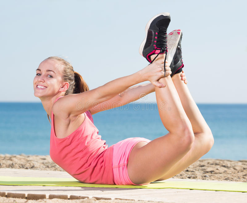 Lächelnde sportliche Frau, die Yoga ausübt lizenzfreie stockbilder