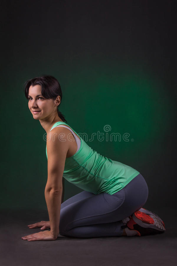 Lächelnde sportliche Frau, Eignungsfrau, die auf einem dunklen Hintergrund mit grüner Hintergrundbeleuchtung sitzt stockbilder