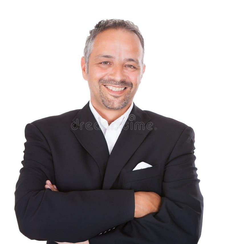 Lächelnde stehende Arme des reifen Geschäftsmannes gekreuzt lizenzfreie stockfotos