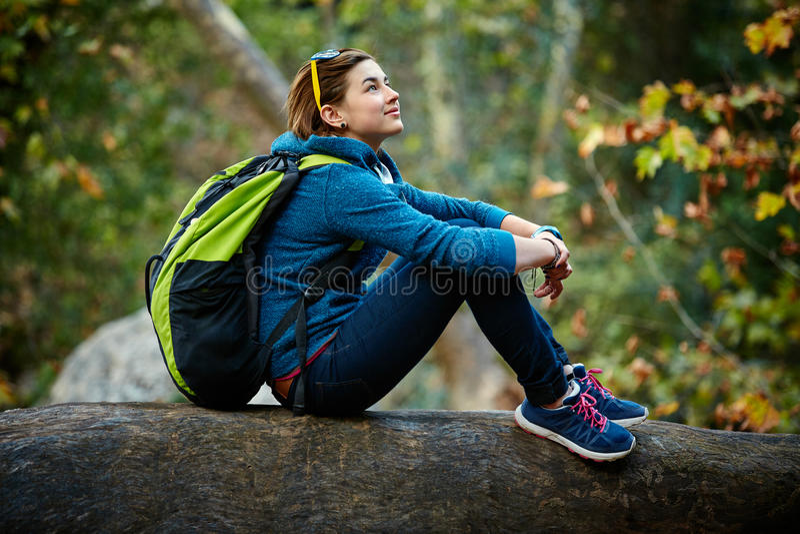 Lächelnde stehende Außenseite des Frauenwanderers im Wald stockfotos