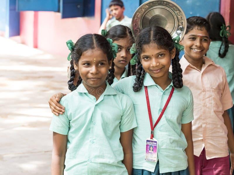 Lächelnde Stellung der besten Kinderfreundmädchen-Mitschüler mit der Hand auf Schulter in der Schule Multiethnisches Schulkinderg lizenzfreies stockbild