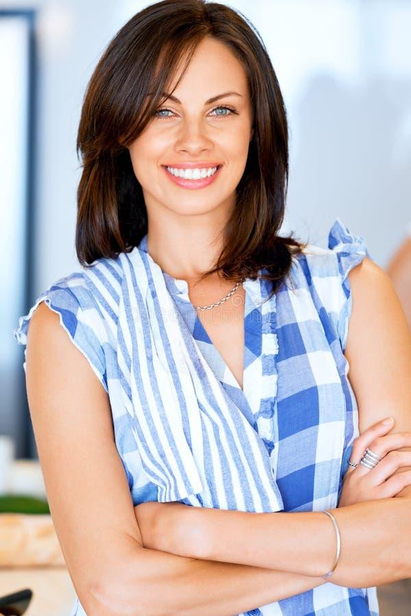 Lächelnde Stellung der jungen Frau mit Geschirrtuch stockfotos