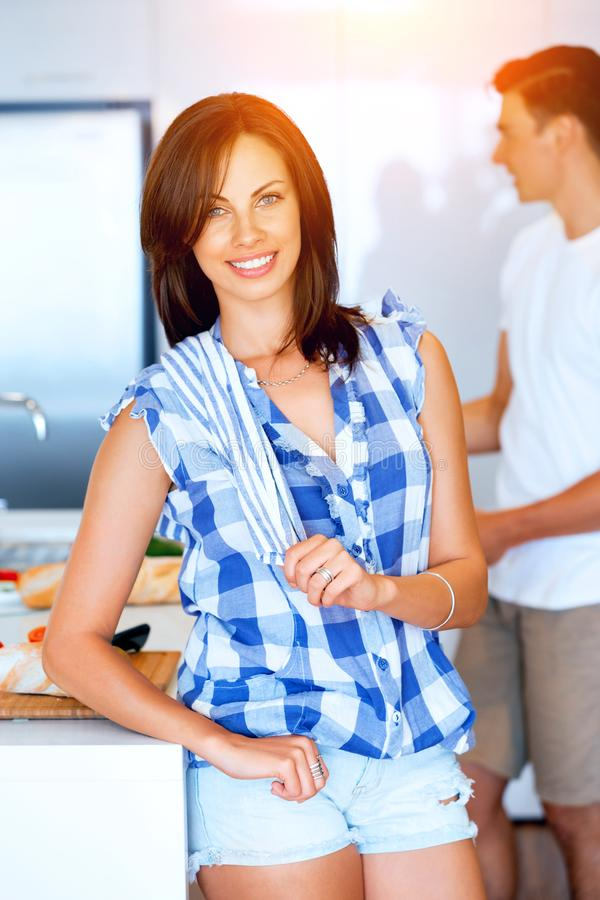Lächelnde Stellung der jungen Frau mit Geschirrtuch lizenzfreie stockbilder