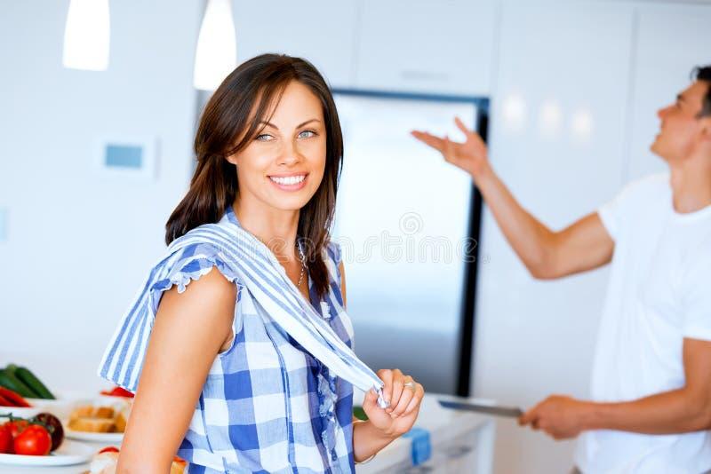 Lächelnde Stellung der jungen Frau mit Geschirrtuch lizenzfreie stockfotos