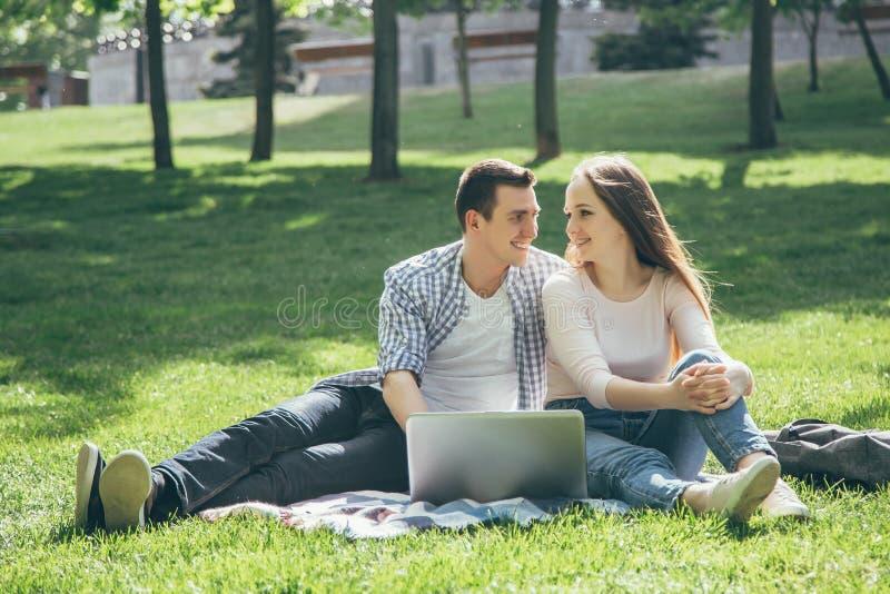 Lächelnde Studenten beim Ablesen und Anwendung des Laptops auf grünem Gras im Park Glückliche Ausbildung lizenzfreie stockbilder