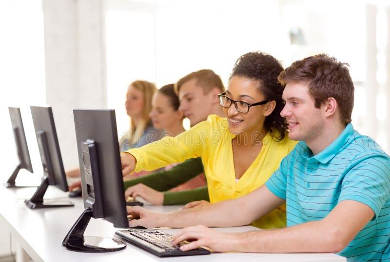 Lächelnde Studenten in der Computerklasse in der Schule stockfotos