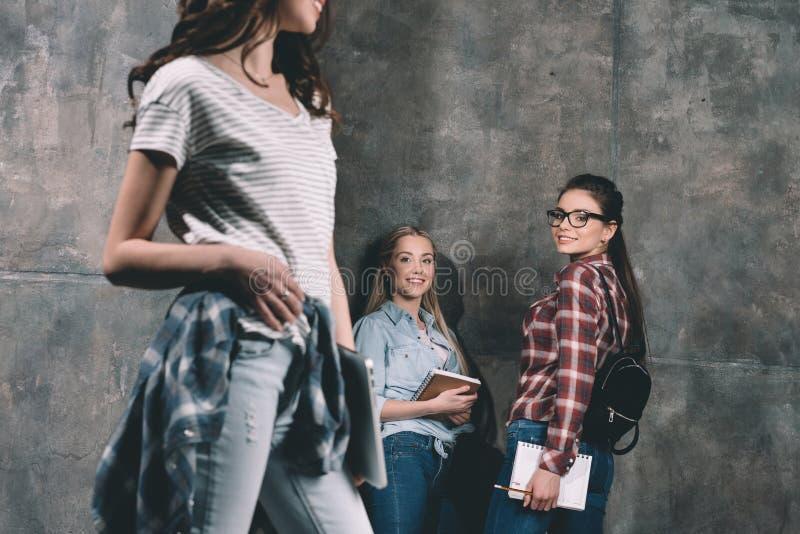Lächelnde Studenten, die auf dem Mädchen steht mit Laptop schauen stockfoto