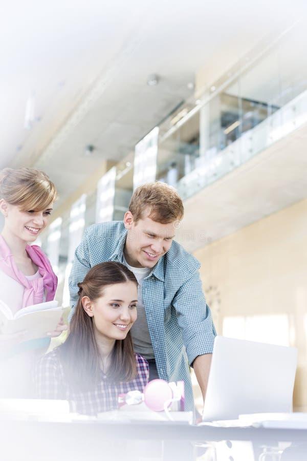 Lächelnde Studenten, die bei Tisch Aufgabe in der Universität tun stockfoto
