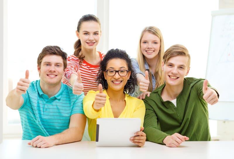 Lächelnde Studenten mit Tabletten-PC-Computer in der Schule stockfotos