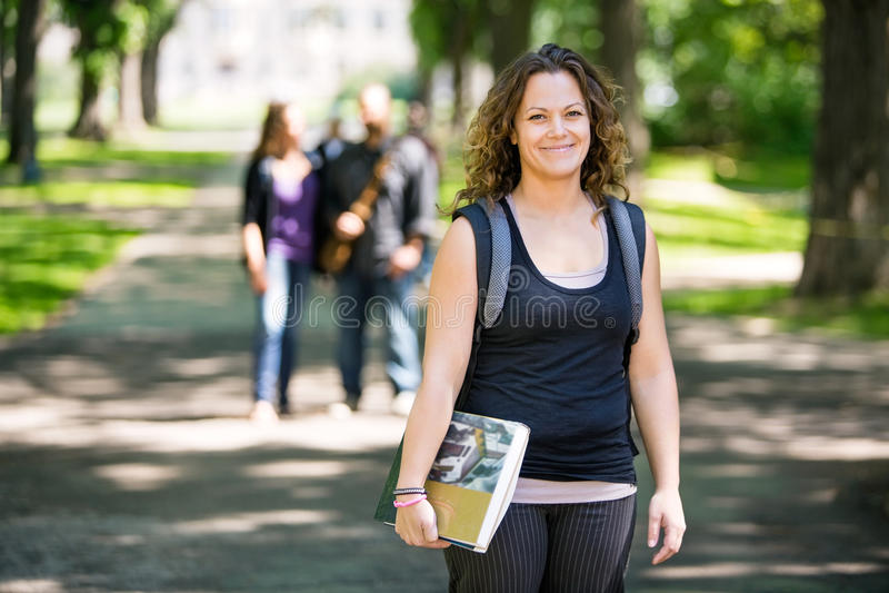 Lächelnde Studenten-Standing On Campus-Straße stockfotografie