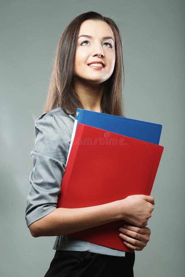 Lächelnde Studentenfrau mit Ordnern lizenzfreie stockbilder