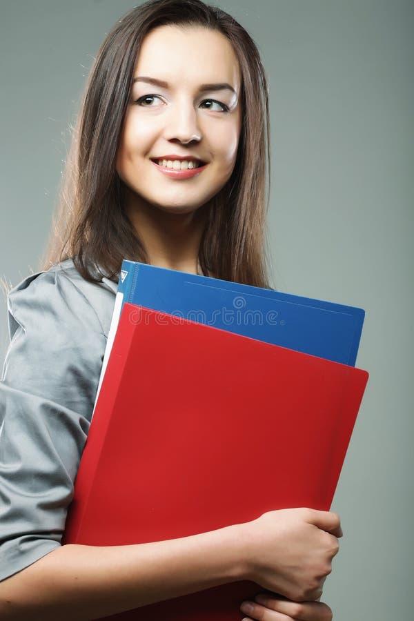 Lächelnde Studentenfrau mit Ordnern stockbild