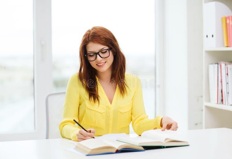 Lächelnde Studentenmädchen-Lesebücher in der Bibliothek lizenzfreies stockbild