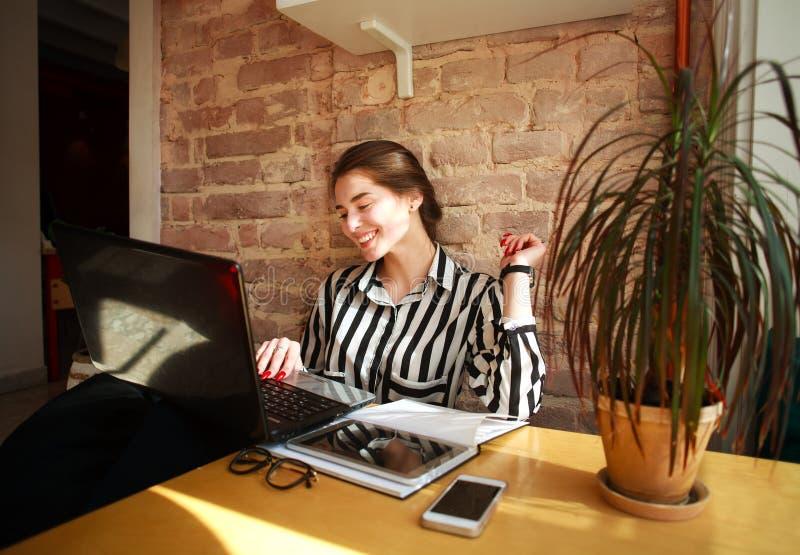 Lächelnde Studentin mit Bildung des Laptops bei Tisch zu Hause lizenzfreie stockbilder