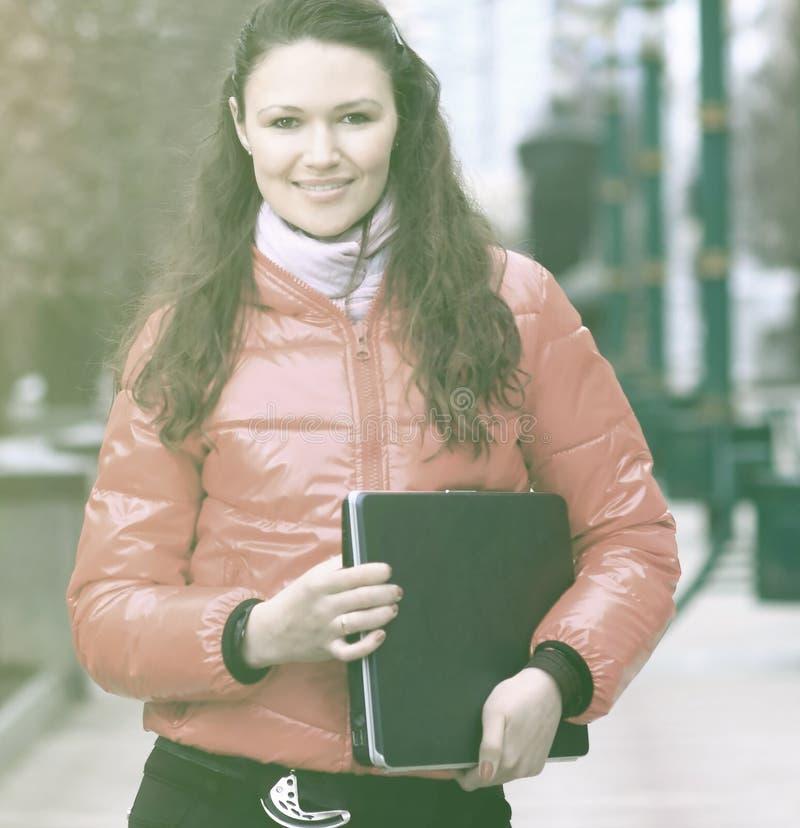 Lächelnde Studentin mit Laptop auf dem Hintergrund einer Winterstadt lizenzfreie stockbilder