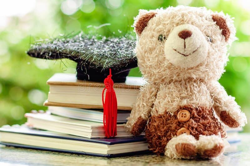 Lächelnde Teddybärpuppe mit quadratischer akademischer Kappe und Stapel BO stockfotografie