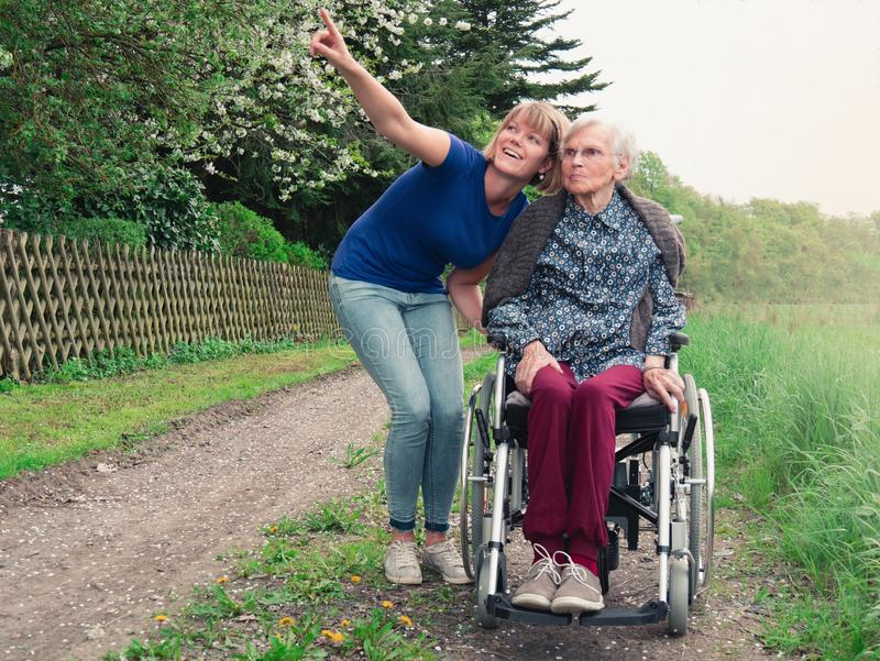 Lächelnde Tochter und Großmutter mit Rollstuhl lizenzfreies stockfoto
