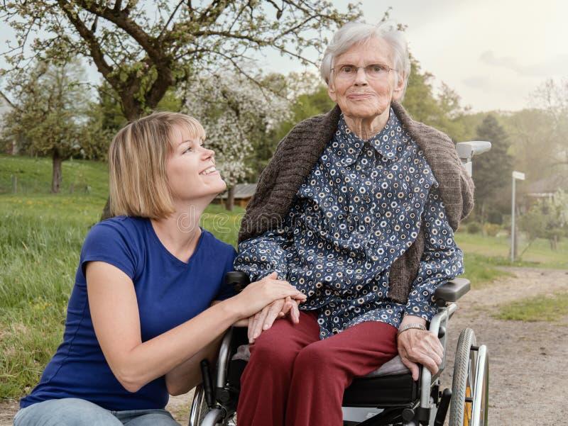 Lächelnde Tochter und Großmutter mit Rollstuhl stockfotografie
