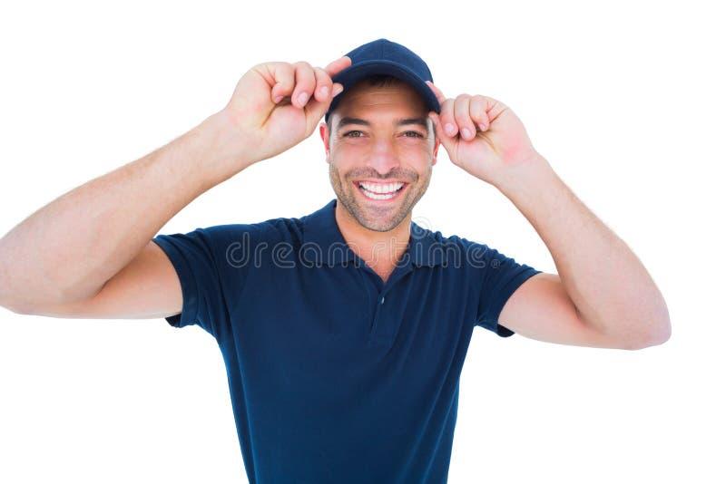 Lächelnde tragende Kappe des Lieferers auf weißem Hintergrund stockbild
