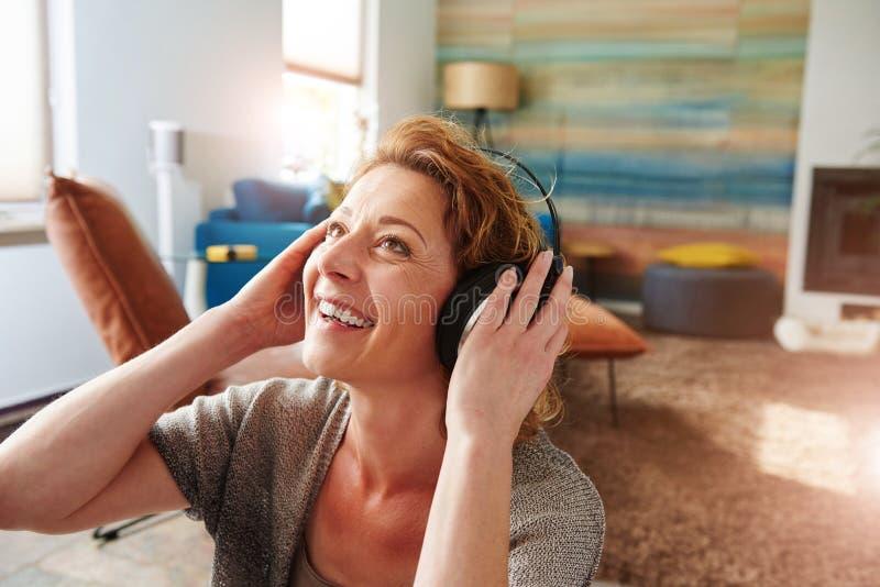 Lächelnde tragende Kopfhörer der Frau und Hören Musik stockfoto