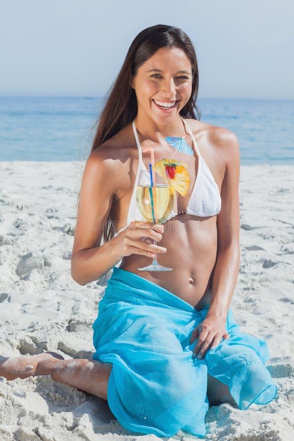 Lächelnde tragende Saronge und Halten der Frau des Cocktails stockbild