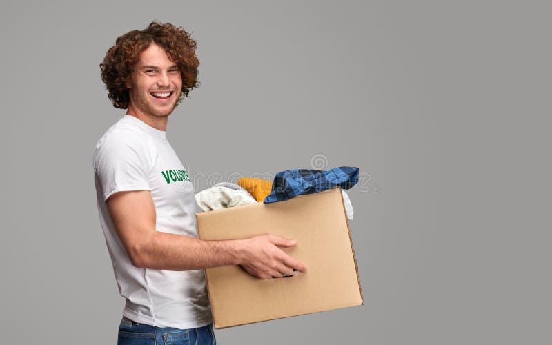 Lächelnde tragende Spenden des Freiwilligen stockfoto